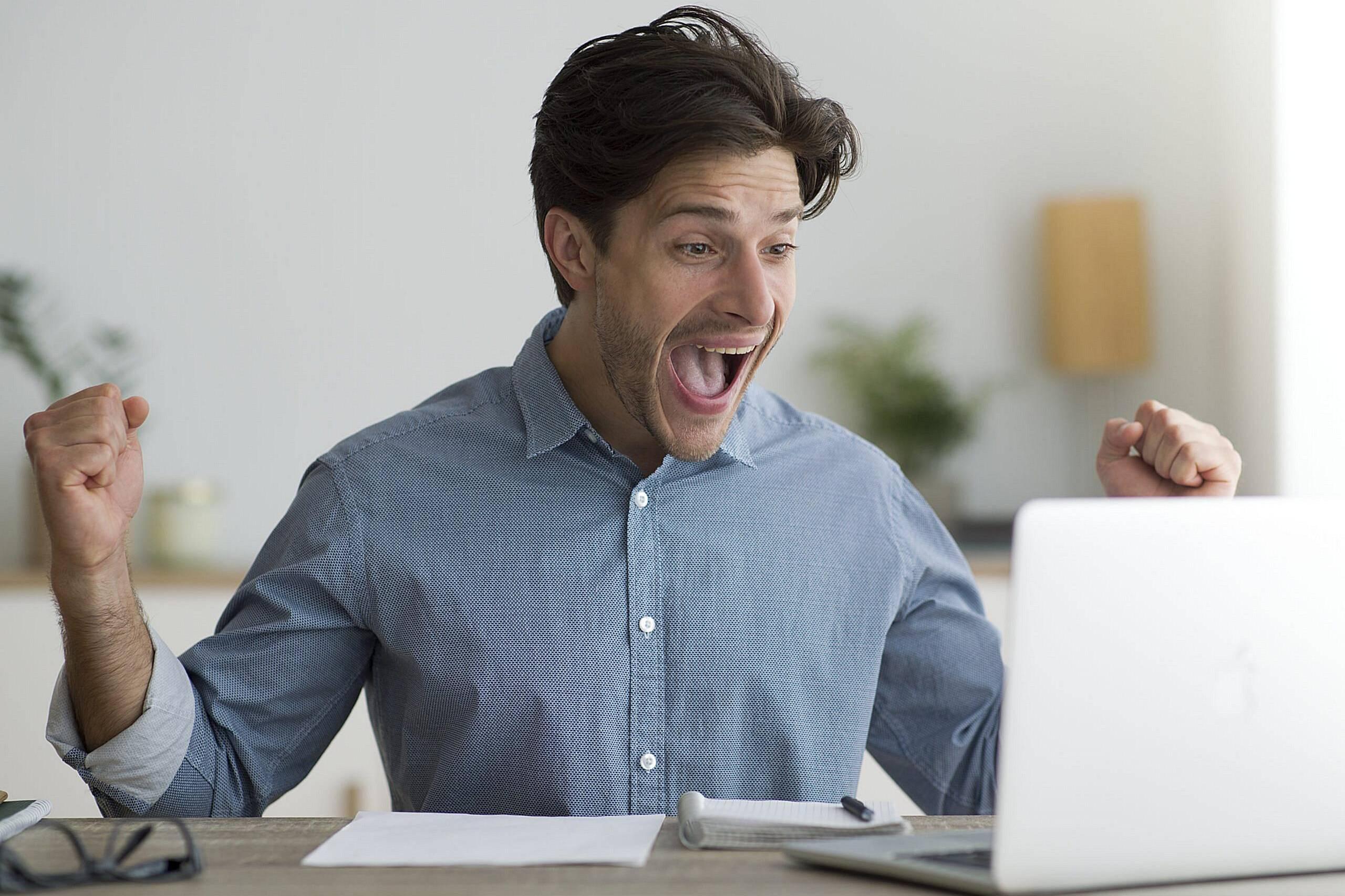 Hombre festejando alegre delante de una computadora
